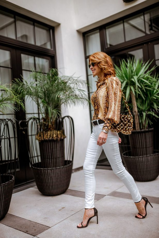 golden color snake print button-up top with white jeans