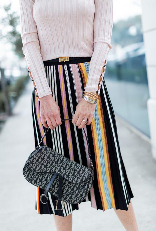 Multi-color skirt with pale pink top and Dior saddlebag