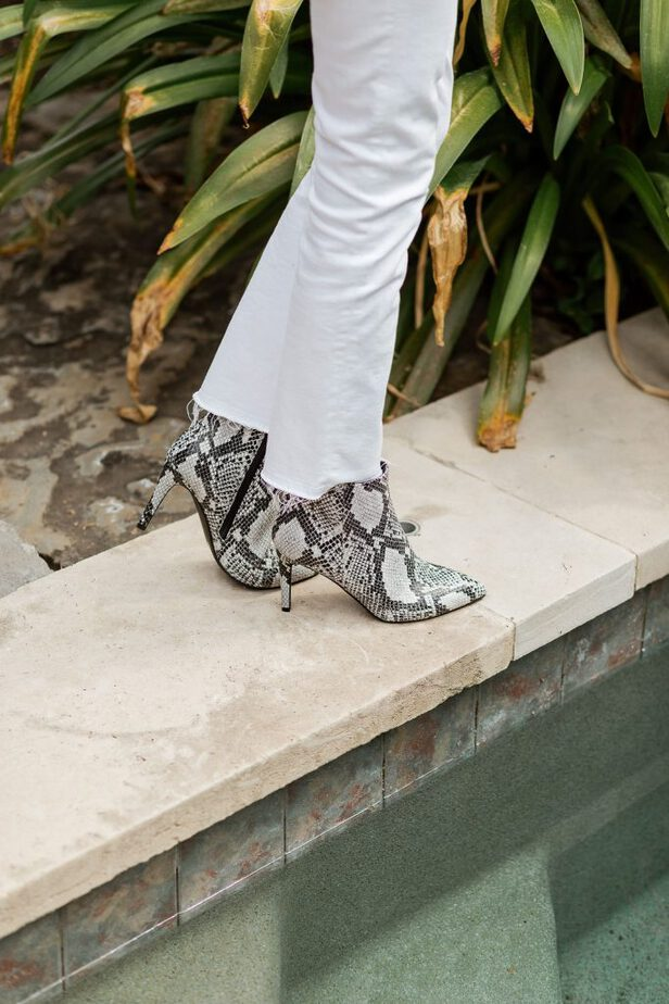 a woman wearing snake print booties