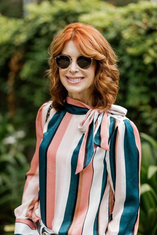 a striped blouse and shades on a red head