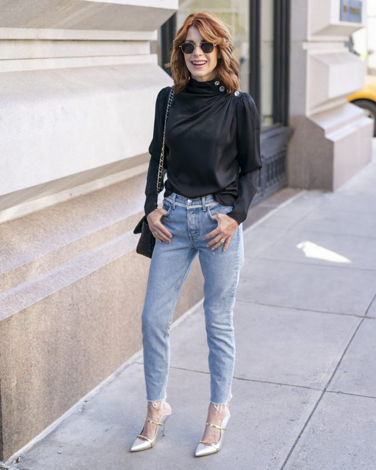 Over 50 blogger wearing black blouse and jeans from Intermix paired with a Chanel purse