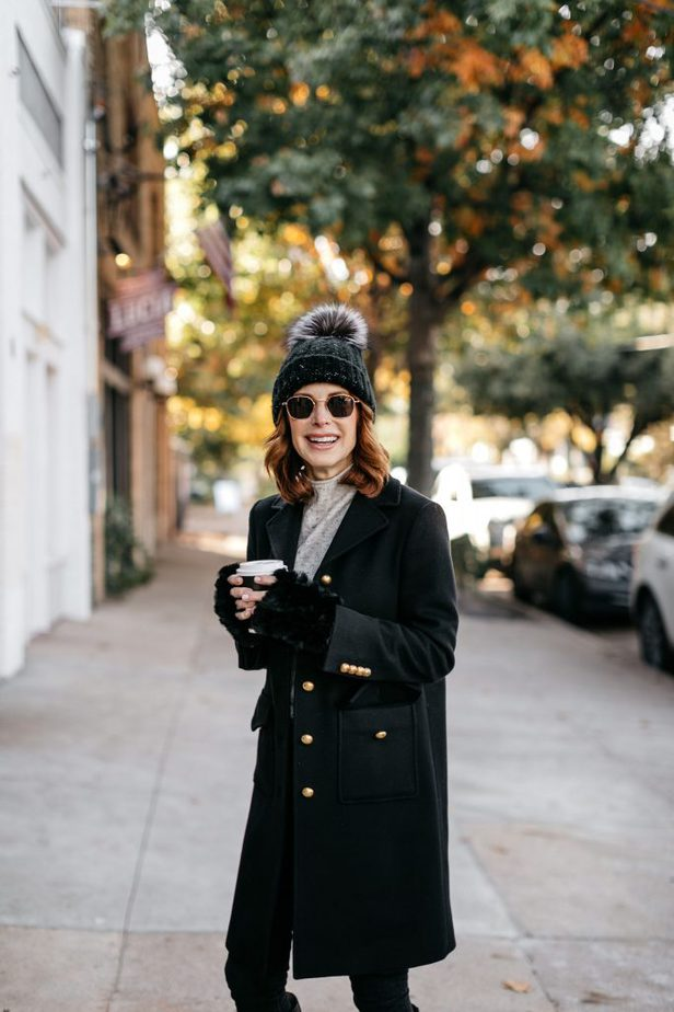 Cathy Williamson wearing black Gucci coat paired with Ray Ban sunglasses and a beanie