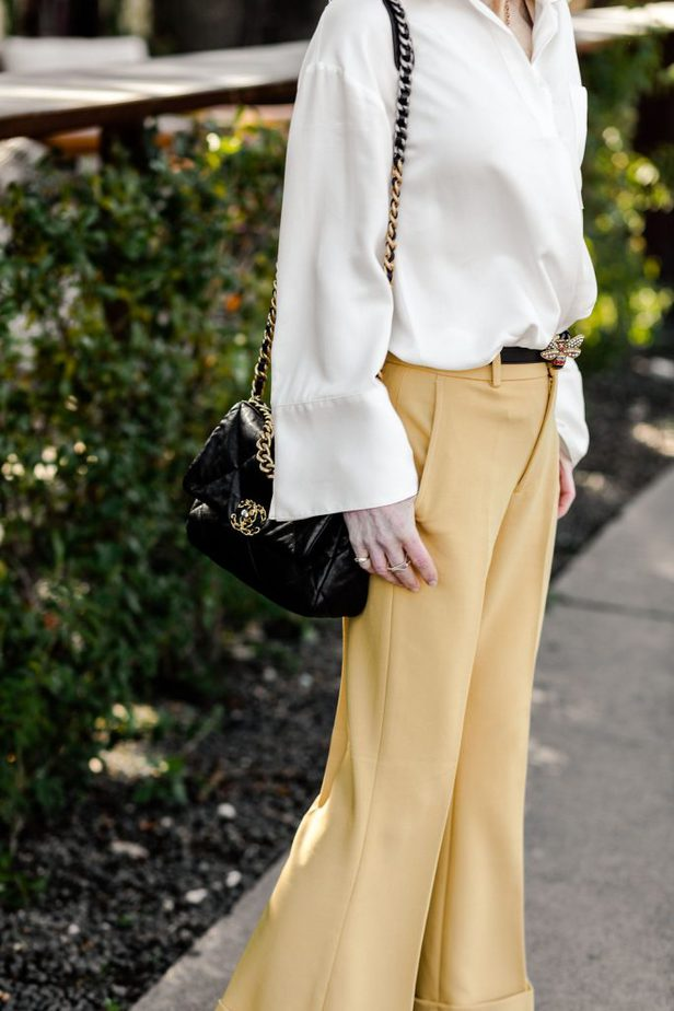 Cathy Williamson wearing blouse and yellow pants from Club Monaco with Chanel purse and Gucci belt