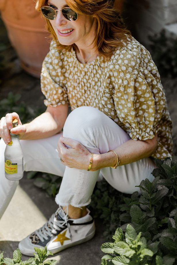 Cathy Williamson wearing white denim jeans with Golden Goose sneakers and Madewell blouse