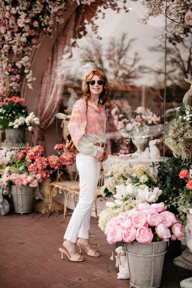 Woman wearing cotton candy color blouse and white pants from Pilcro