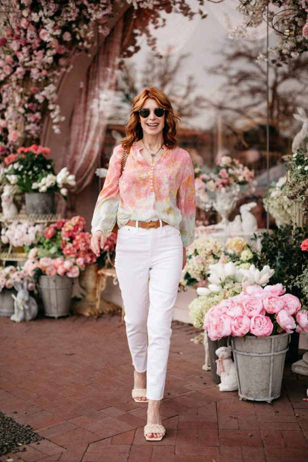 woman standing outside a store wearing pastel color blouse