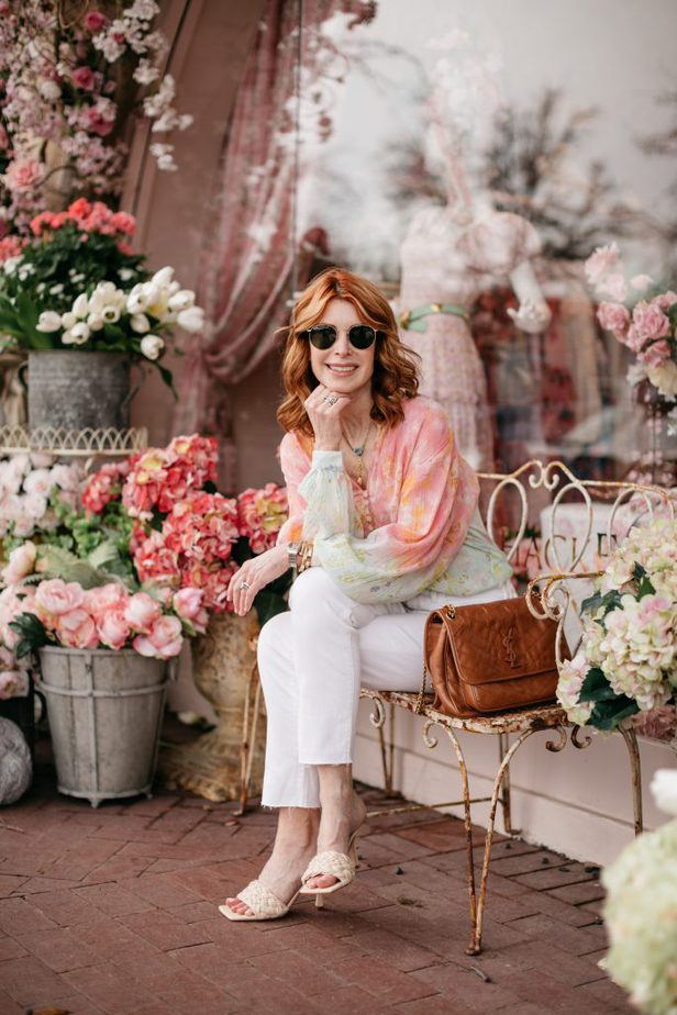 woman sitting outside a store wearing a cotton candy color top