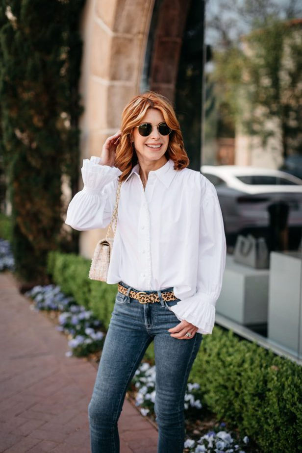 woman with red hair, wearing white shirt, and jeans