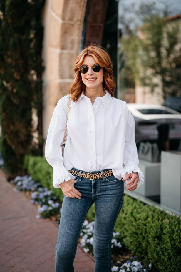 woman wearing white shirt and jeans pictured outdoors
