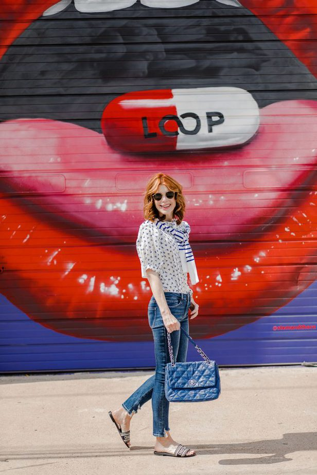 Dallas Blogger in Floral Puffed Sleeve Top from Rebecca Taylor, jeans, and holding a glue bag