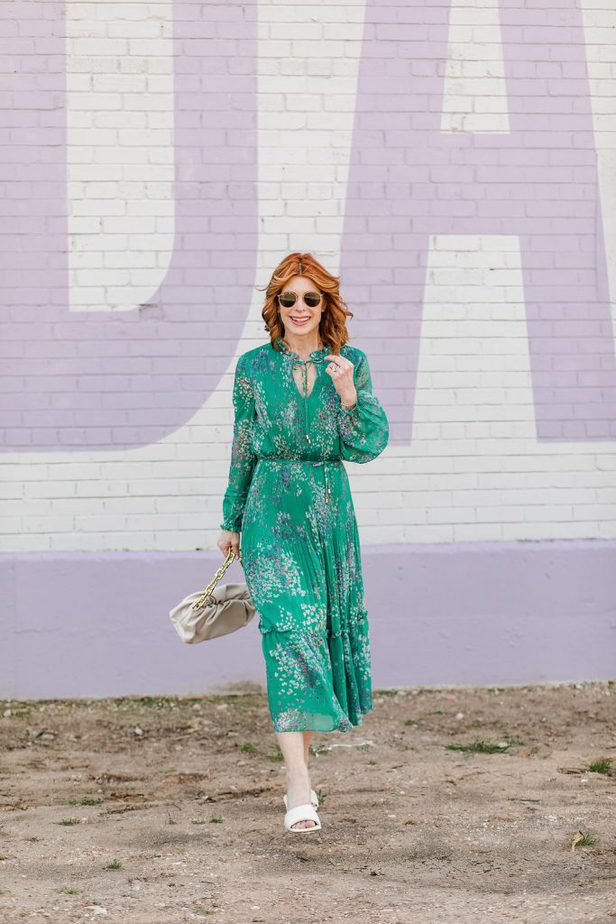 woman wearing the Perfect Multi-Occasion Dress in green, white sandals, and holding a bag