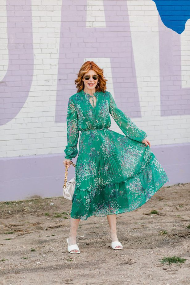 woman wearing Perfect Multi-Occasion Dress in green and holding the bottom part