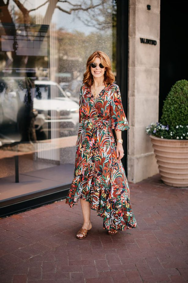 woman wearing colorful dress, sunglasses, and falts