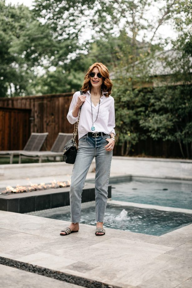 woman near the pool and wearing White Button-Down. jeans, and flats