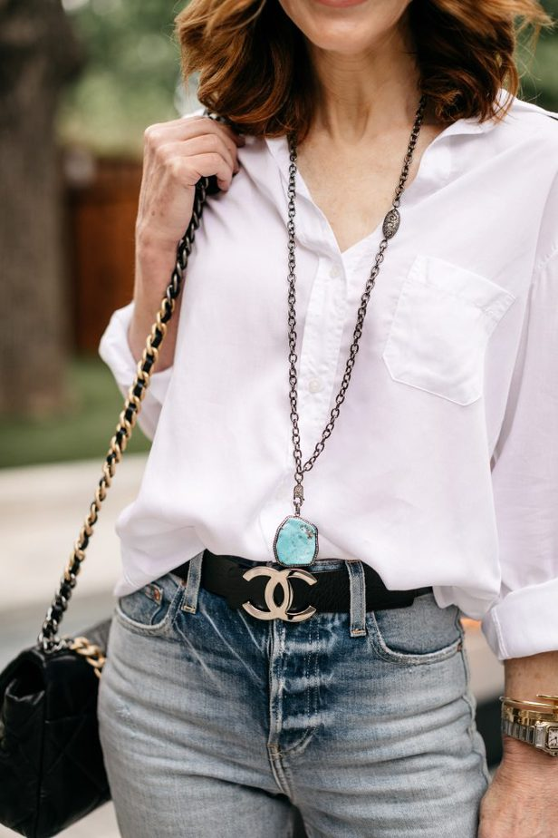 woman wearing White Button-Down, necklace and has a black sling bag