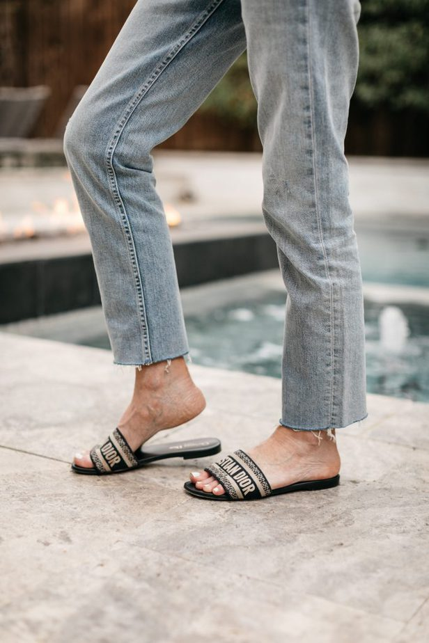 woman wearing jeans and christian dior slides