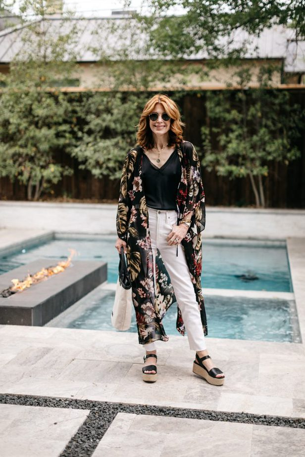 woman wearing black top, white pants, and platform sandals at the poolside