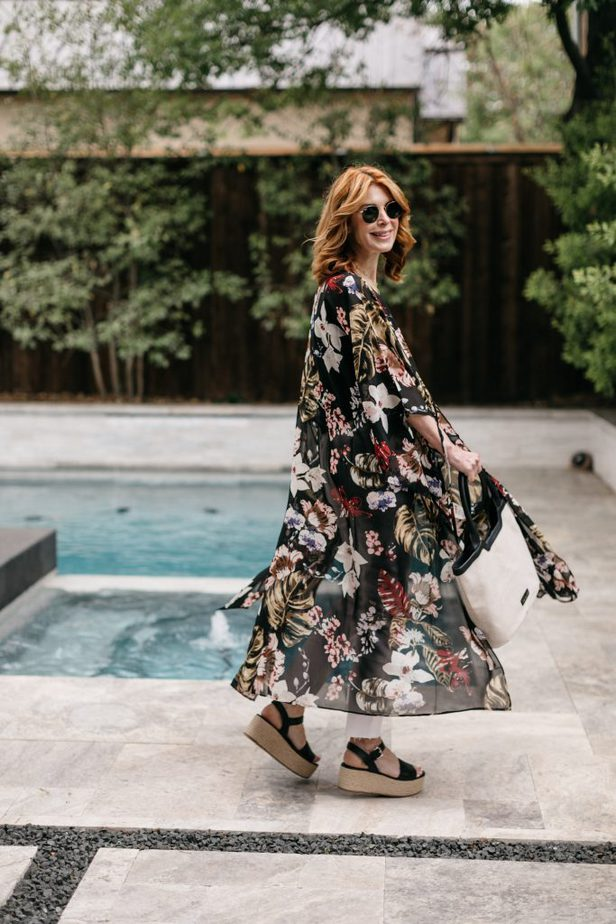 woman wearing black top, white pants, floral kimono and platform sandals at the poolside