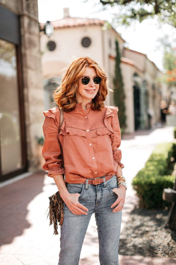 woman earing sunglasses, ruffled top, and jeans