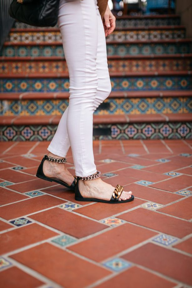 woman's white pants and flats with gold chain