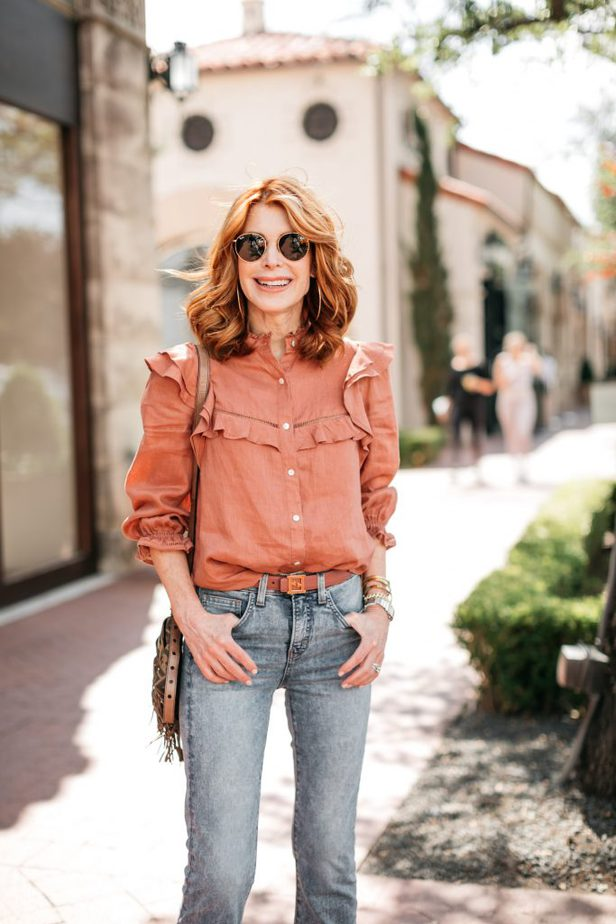 woman earing sunglasses, ruffled top one of the top ten statement tops, and jeans