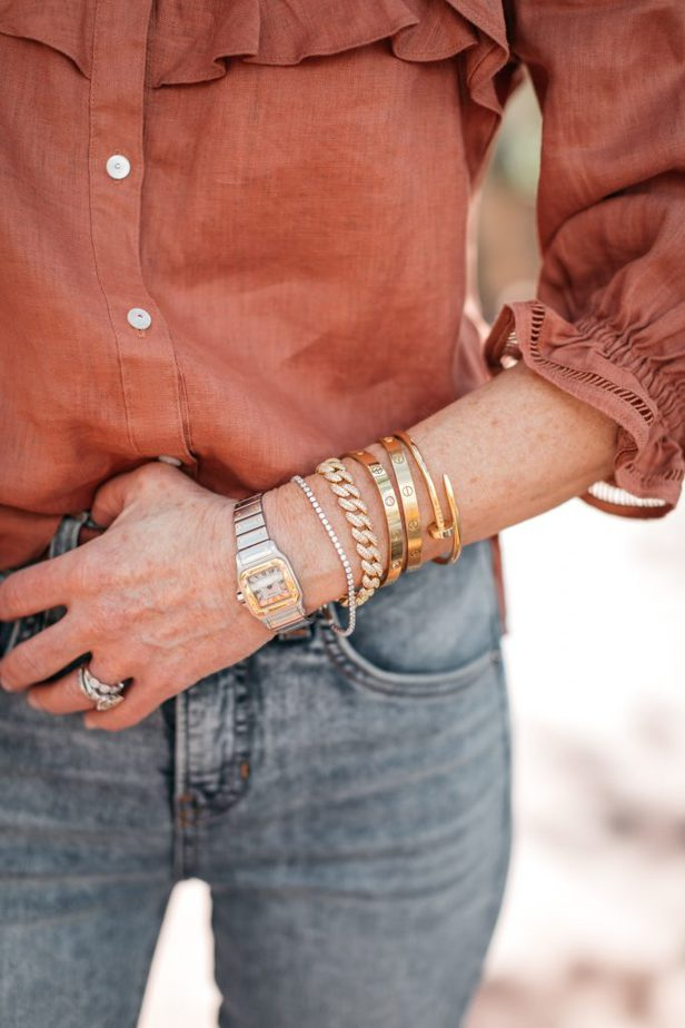 woman's arm wearing bracelets, watch, and a ring