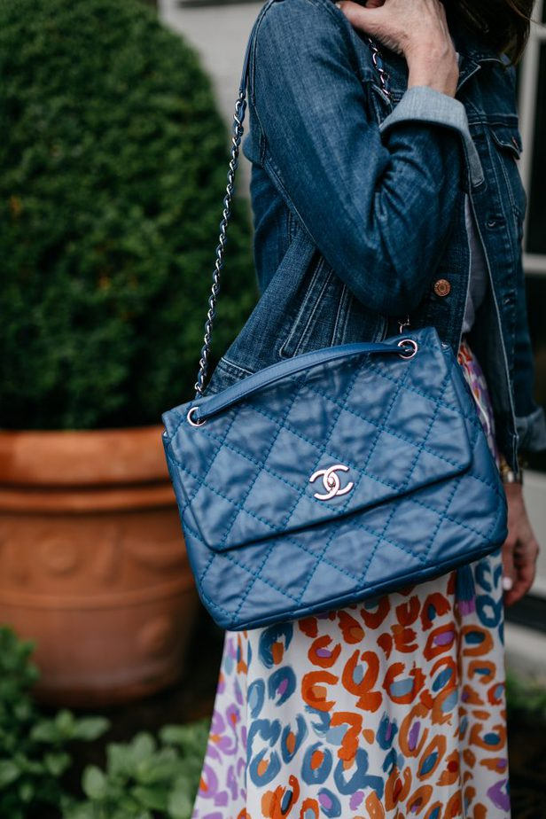 blue channel bag on woman wearing skirt and denim jacket