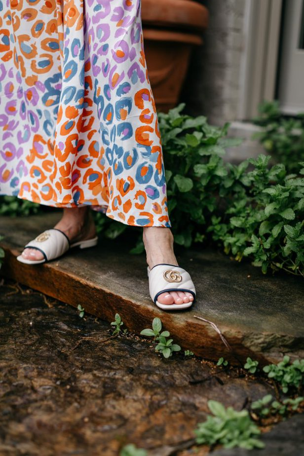 woman wearing channel slides and happy print skirt