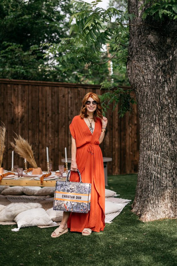 woman smiling, standing near a tree and wearing orange CHIC COVER-UP