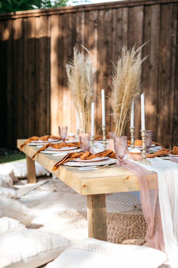 wood table surrounded with white pillows with orange and pink table setup