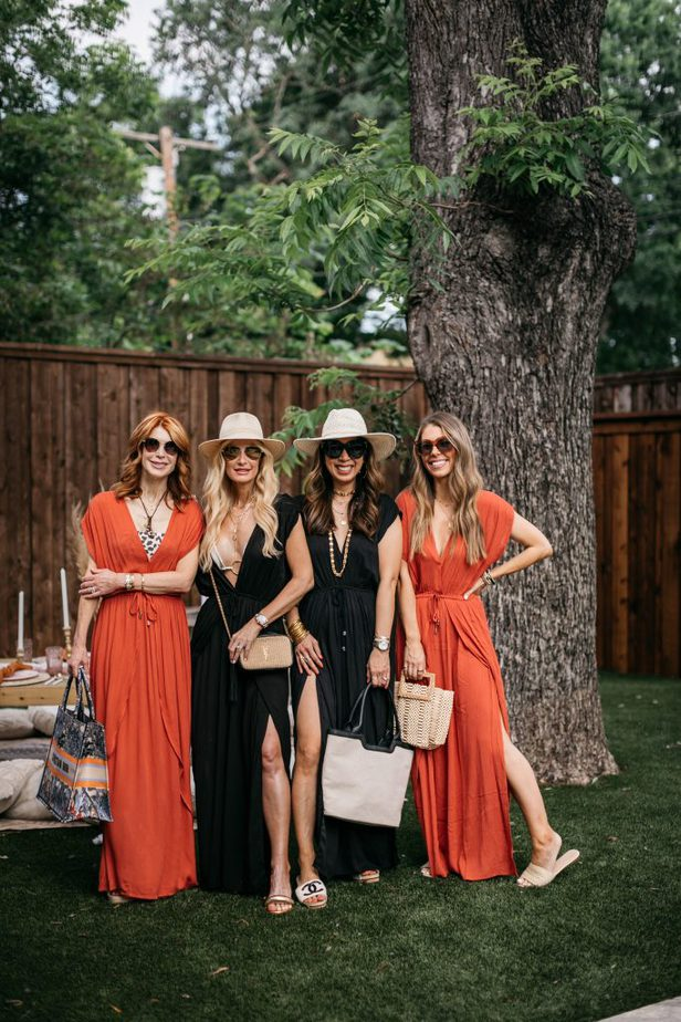 for women standing near a tree and a table setup and they are wearing orange CHIC COVER-UP