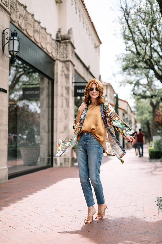 woman walking and wearing flowy top and jeans