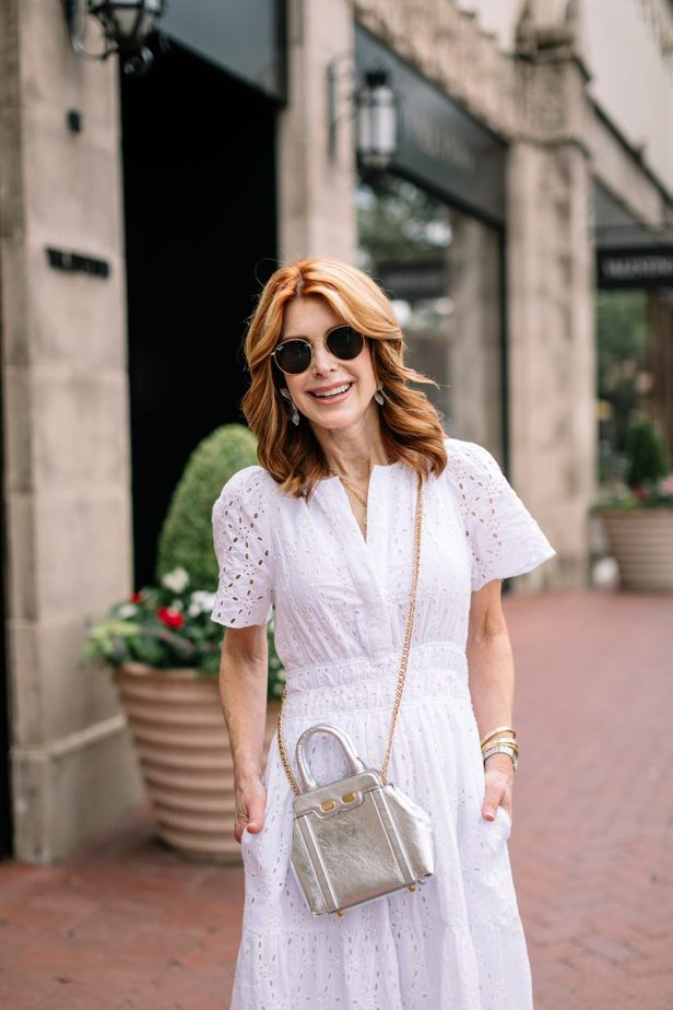 One of the Cool Summer Dresses is a White Eyelet Dress and Silver Bene Handbag on Dallas Blogger