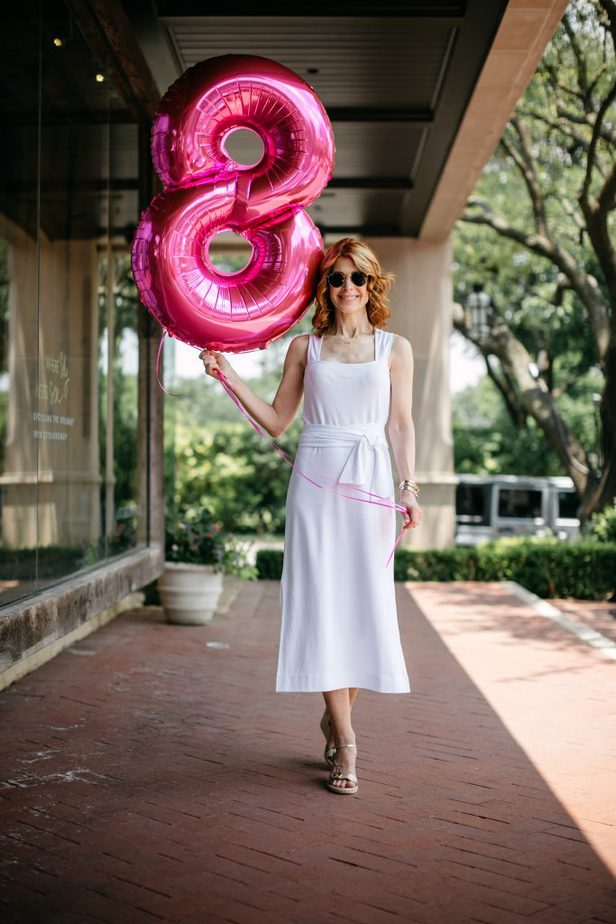 woman wearing white and holding a number 8 balloon for EIGHT YEAR CANCERVERSARY