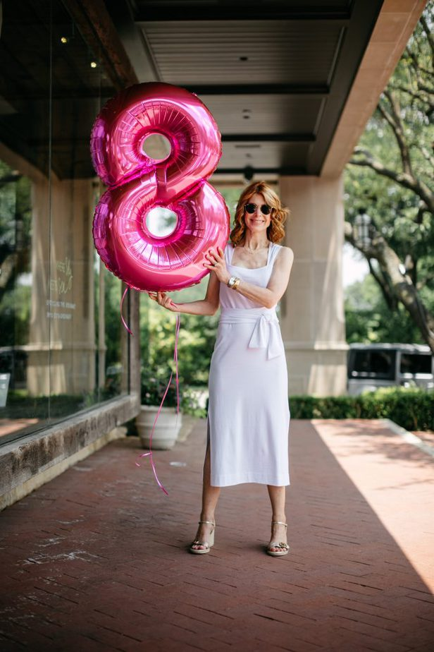 woman smiling wearing white dress and holding a number 8 balloon for EIGHT YEAR CANCERVERSARY