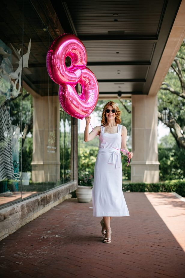 woman holding a balloon with number eight