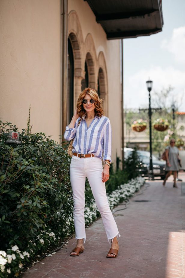woman posing and wearing CLASSIC STRIPED BUTTON-DOWN and white pants