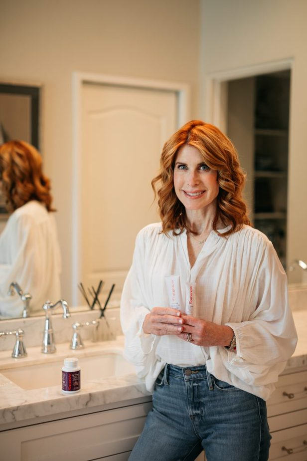woman in the bathroom holding WOMANESS products