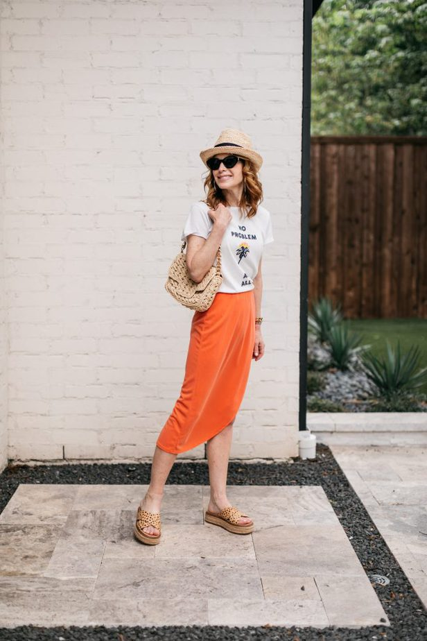 woman posing and wearing white top and orange skirt