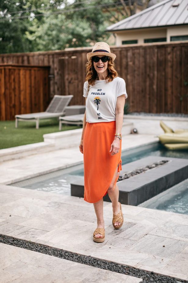 woman standing near the pool and happy as It's Still Summer