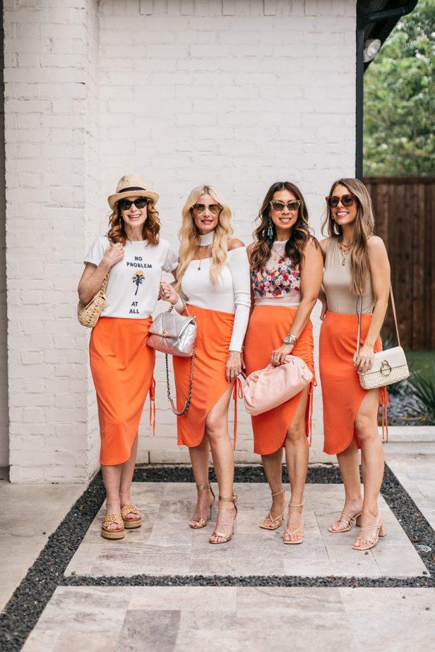 four women wearing orange skirt and holding their purses celebrating It's Still Summer