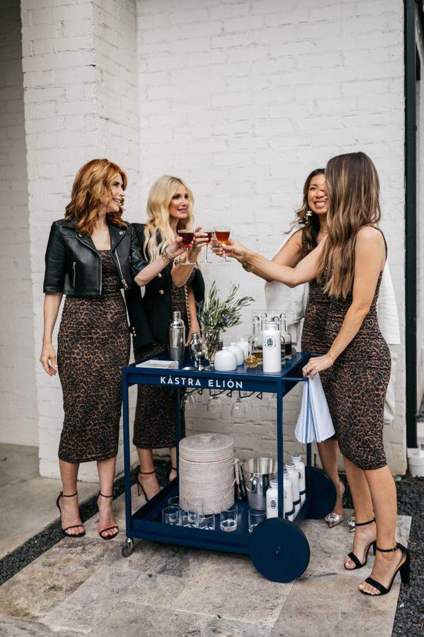 Dallas Bloggers in Good American leopard 90's tank dress standing near a bar cart