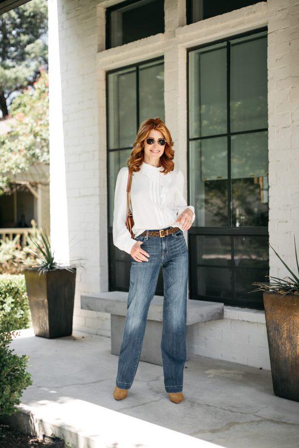 woman wearing white blouse, denim jeans, brown belt