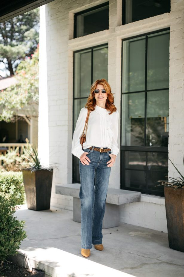 woman wearing jeans. blouse, and sunglasses and fingers on her pocket