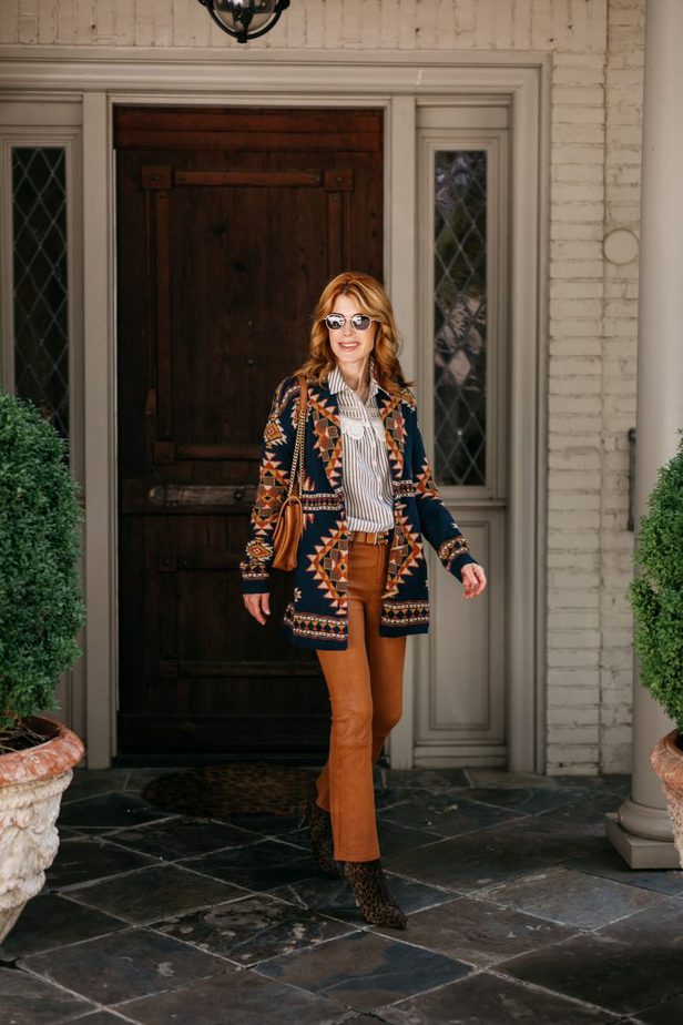 woman wearing printed sweater for sweater weather, orange pants, and striped shirt