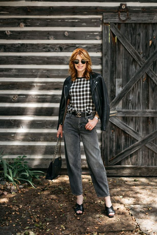 woman posing in plaid top, leather jacket and black jeans