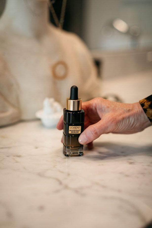 person holding a bottle of L'Oréal Paris Midnight Serum