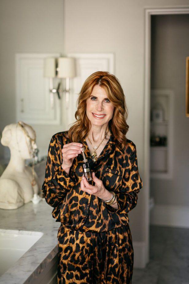 woman in her bathroom holding L'Oréal Paris Midnight Serum