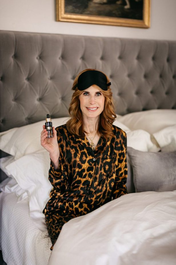 woman on her bed and holding a facial serum bottle