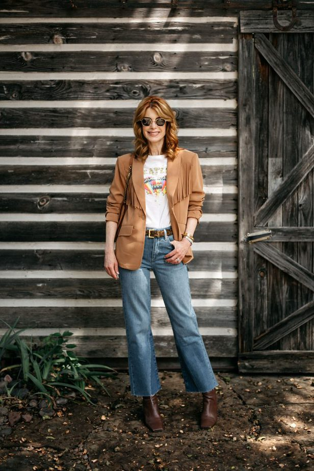 woman wearing shirt, fringe blazer, and jeans